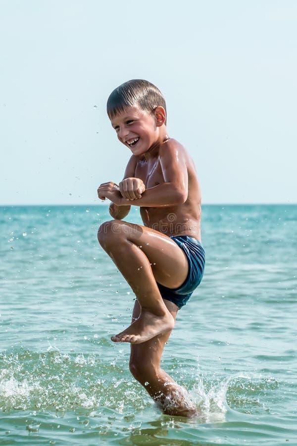Muchacho sano que salta en agua imagen de archivo libre de regalías