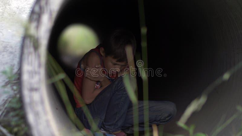 Muchacho solo sin hogar que oculta dentro de un túnel del drenaje de la helada que intenta mantener caliente foto de archivo libre de regalías