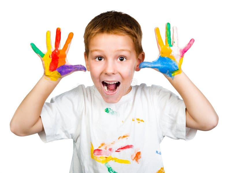 Muchacho sonriente con las manos en pintura imagen de archivo