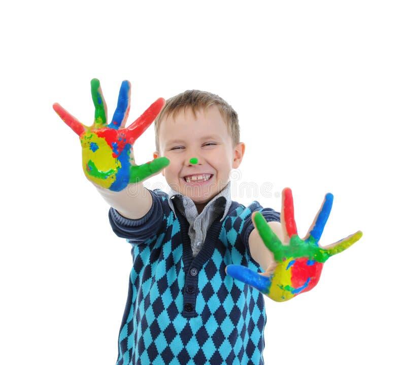 Muchacho sonriente con las palmas pintadas por una pintura. foto de archivo libre de regalías