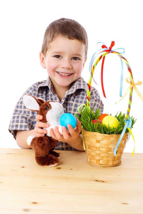 Muchacho sonriente con los huevos y el conejito de Pascua fotos de archivo