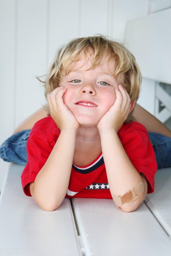 Muchacho sonriente con un codo vendado imágenes de archivo libres de regalías