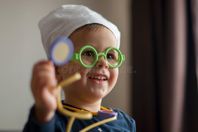 Muchacho sonriente de 2 años que juega al doctor Equipamiento médico del juguete que lleva imagenes de archivo