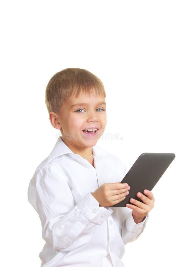 Muchacho sonriente de la lectura con el libro electrónico. Aislado foto de archivo libre de regalías