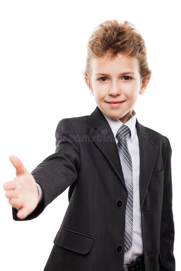 Muchacho sonriente del niño en traje de negocios que gesticula el saludo de la mano o el apretón de manos de la reunión foto de archivo