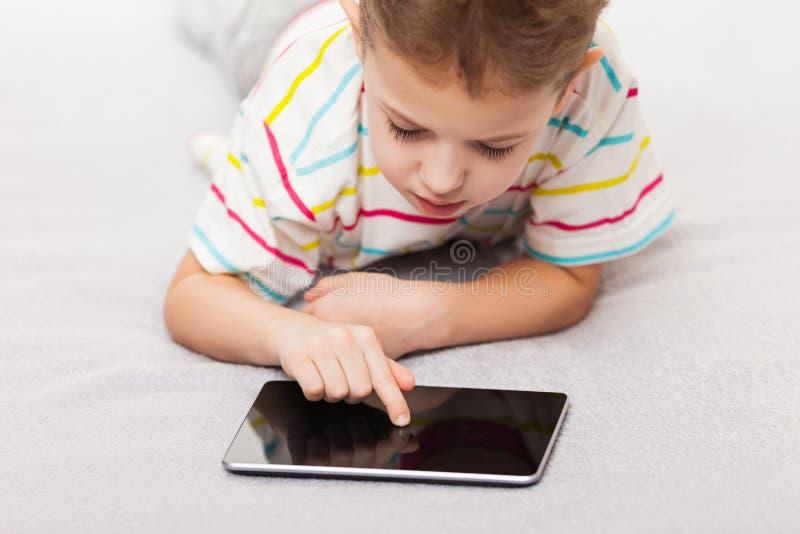 Muchacho sonriente del niño que juega a juegos o que practica surf Internet en la tableta co fotos de archivo libres de regalías