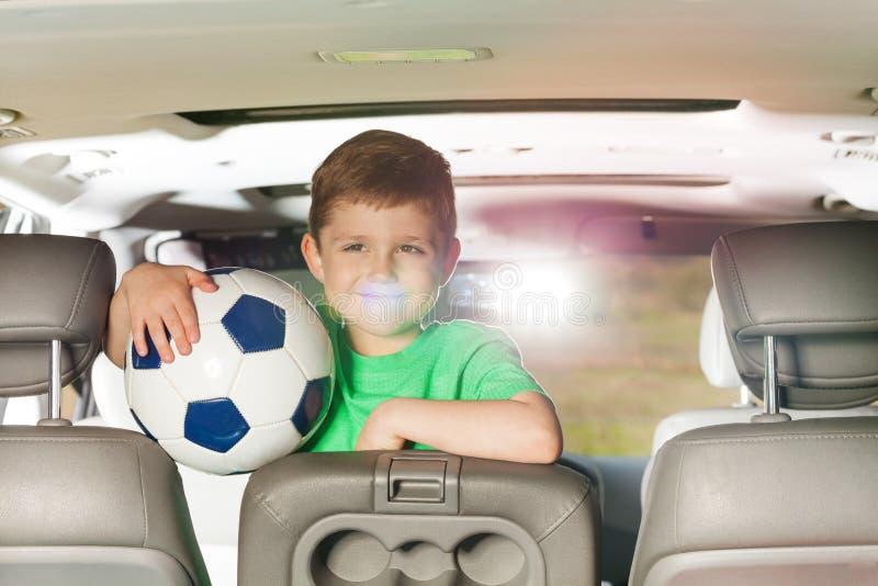 Muchacho sonriente del niño que sostiene el balón de fútbol dentro del coche imágenes de archivo libres de regalías