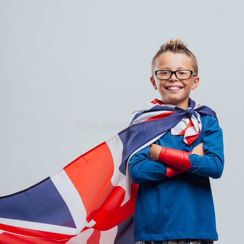 Muchacho sonriente del super héroe con el cabo británico de la bandera foto de archivo