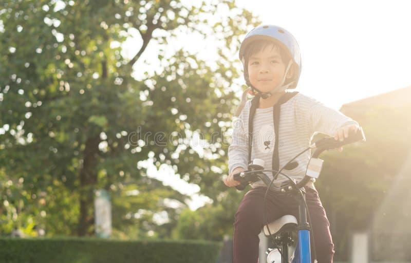 Muchacho sonriente en el casco de seguridad que monta su bici imagenes de archivo