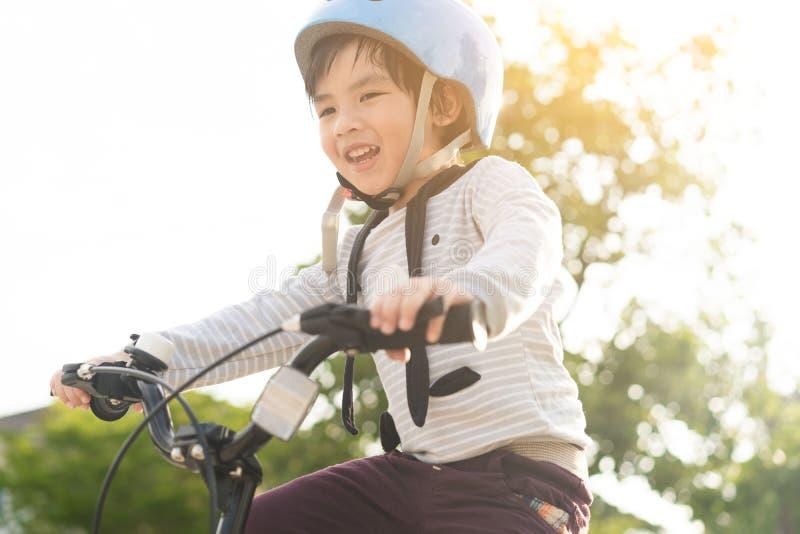 Muchacho sonriente en el casco de seguridad que monta su bici imágenes de archivo libres de regalías