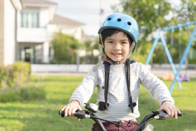 Muchacho sonriente en el casco de seguridad que monta su bici foto de archivo