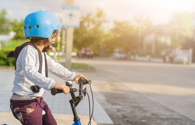 Muchacho sonriente en el casco de seguridad que monta su bici imagen de archivo