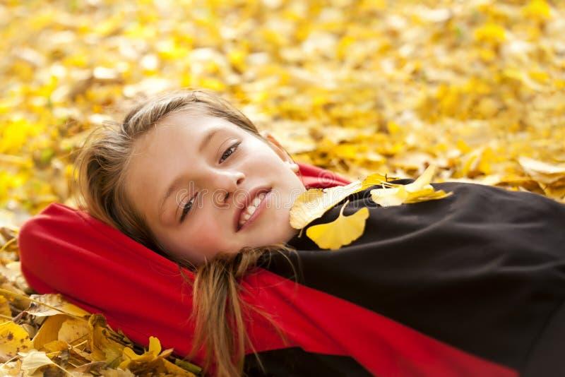Muchacho sonriente en hojas de otoño foto de archivo libre de regalías