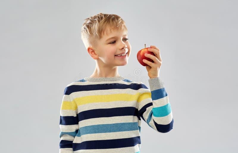 Muchacho sonriente en jersey rayado que come la manzana roja foto de archivo