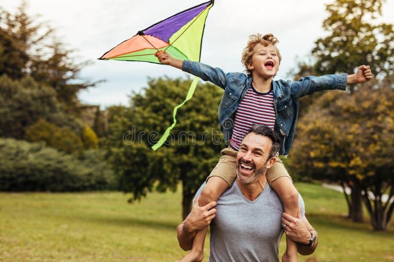 Muchacho sonriente en los hombros de los padres que juegan con la cometa imagen de archivo libre de regalías