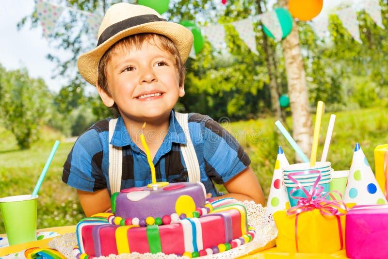 Muchacho sonriente feliz del niño que hace un deseo del cumpleaños imagen de archivo libre de regalías