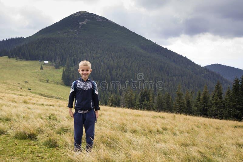 Muchacho sonriente feliz joven del ni?o con la mochila que se coloca en valle herboso de la monta?a en el fondo del paisaje del v foto de archivo libre de regalías