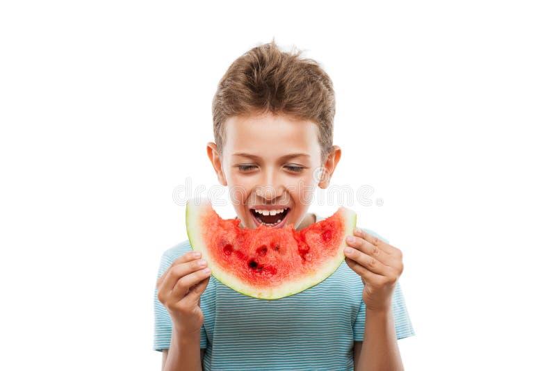 Muchacho sonriente hermoso del niño que lleva a cabo la rebanada roja de la fruta de la sandía imágenes de archivo libres de regalías