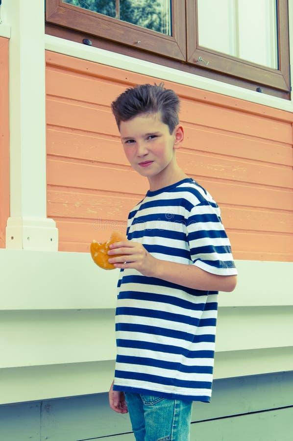 Muchacho sonriente joven con un peinado de moda y una hamburguesa fotos de archivo libres de regalías