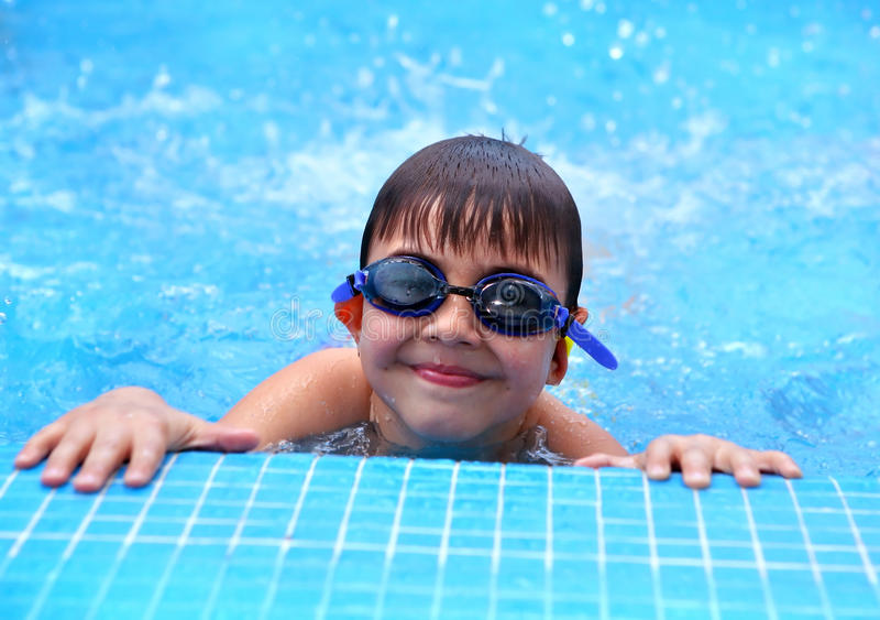 Muchacho sonriente joven feliz en la piscina imagen de archivo