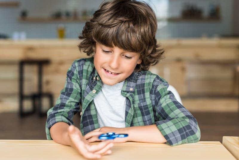 muchacho sonriente lindo con el hilandero de la persona agitada imagen de archivo