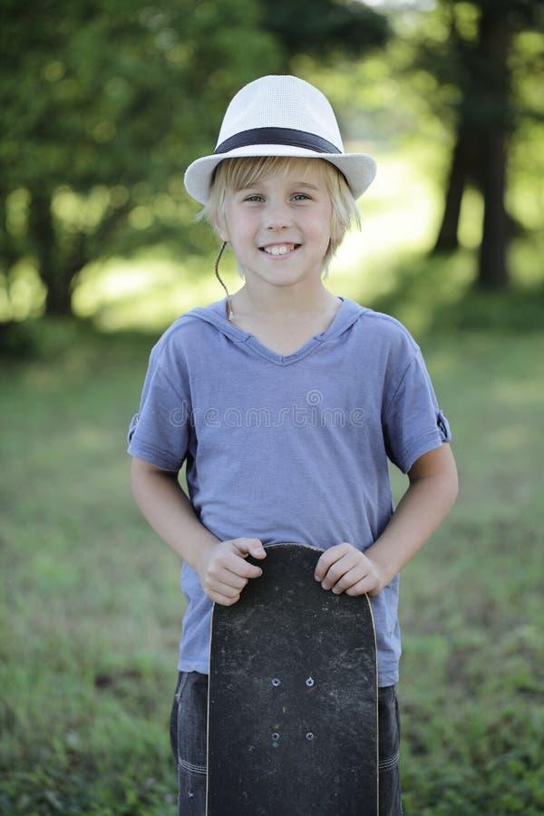 Muchacho sonriente lindo con el monopatín al aire libre imagen de archivo