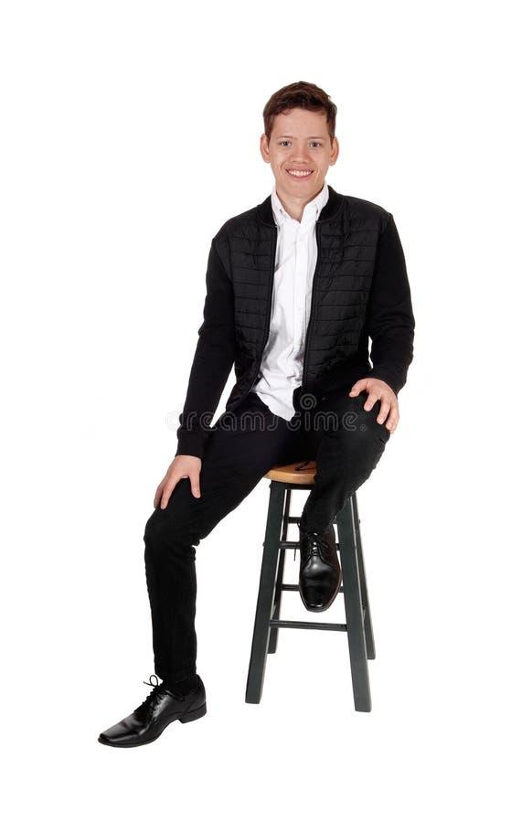 Muchacho sonriente precioso del adolescente que se sienta en una silla fotos de archivo