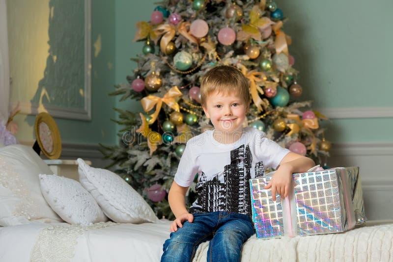 Muchacho sonriente que abraza el cierre de la caja Navidad imagenes de archivo