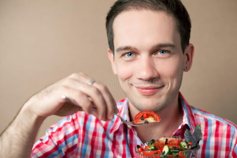Muchacho sonriente que come la ensalada fresca del vegano fotografía de archivo libre de regalías