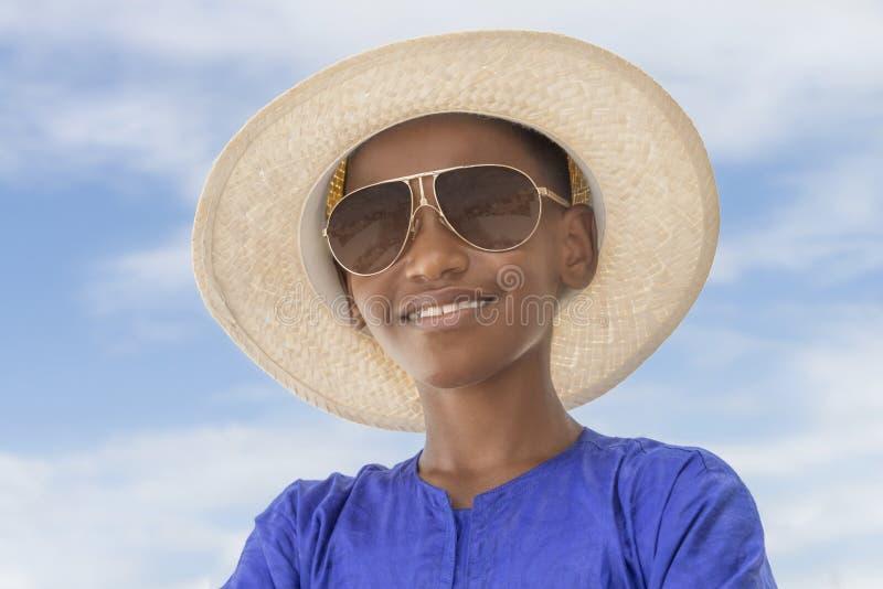 Muchacho sonriente que lleva un sombrero de paja del navegante y un par de gafas de sol imagen de archivo libre de regalías