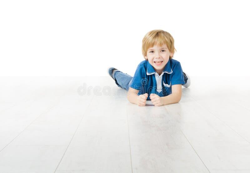 Muchacho sonriente que miente en el suelo blanco foto de archivo libre de regalías