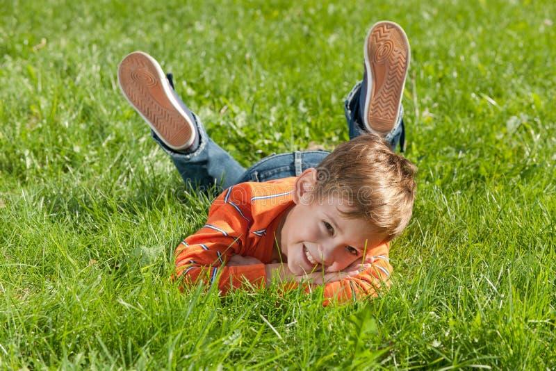 Muchacho sonriente que miente en la hierba fotos de archivo