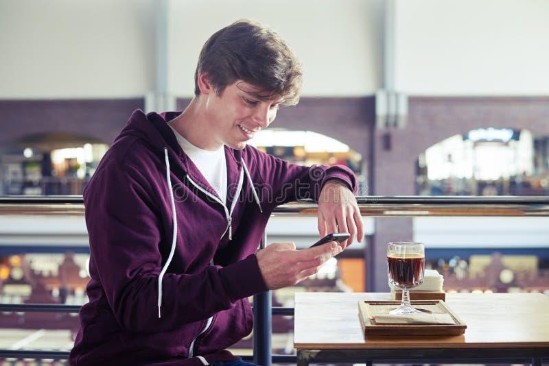 Muchacho sonriente que practica surf en el teléfono móvil que se sienta sobre la taza de café fotos de archivo libres de regalías
