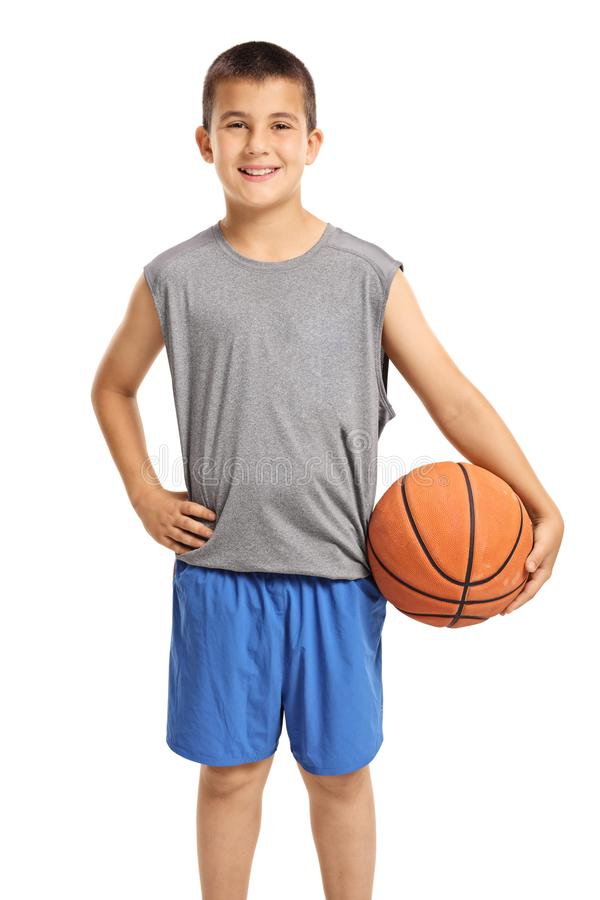 Muchacho sonriente que presenta con un baloncesto imagen de archivo