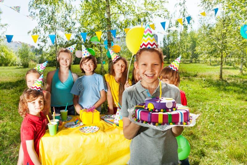 Muchacho sonriente que sostiene la torta de cumpleaños con la vela fotos de archivo