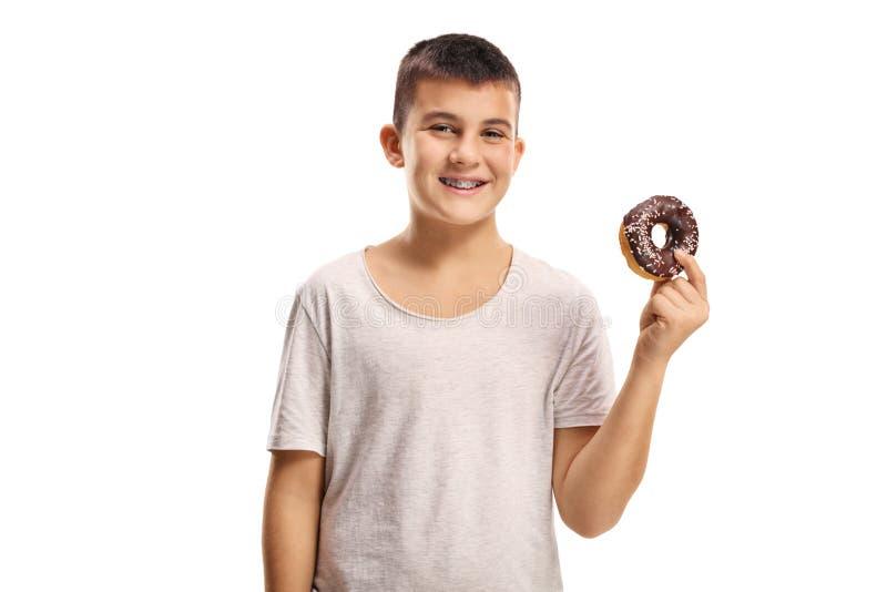 Muchacho sonriente que sostiene un buñuelo del chocolate imagenes de archivo