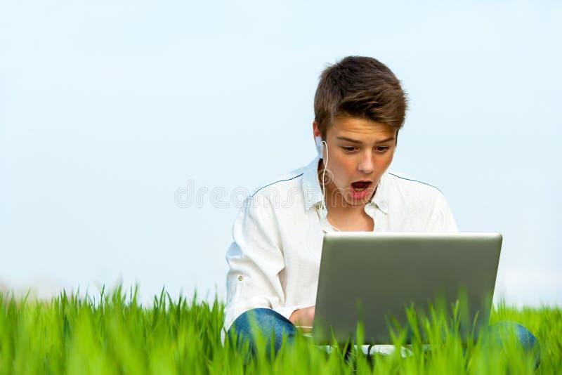 Muchacho sorprendido con el ordenador portátil al aire libre. fotos de archivo