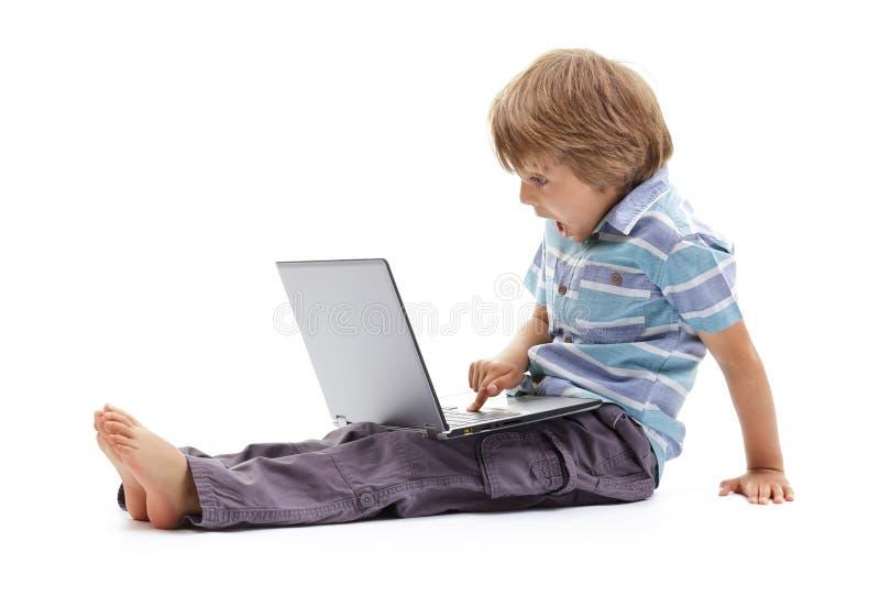 Muchacho sorprendido que usa un ordenador portátil foto de archivo