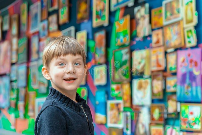 Muchacho sorprendido y alegre en una exposición de pinturas en la galería de arte imagen de archivo libre de regalías