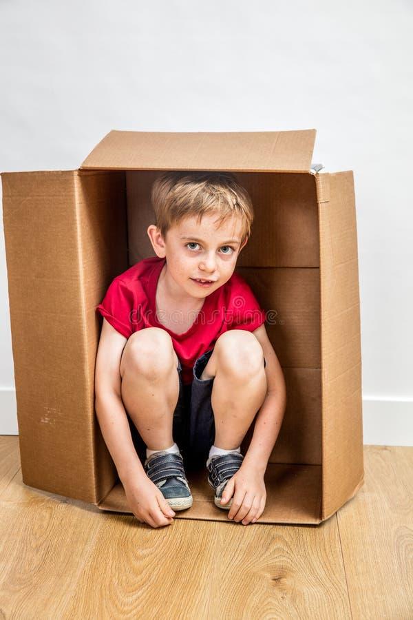 Muchacho tímido que oculta en la caja de cartón que juega en nuevo hogar fotografía de archivo libre de regalías