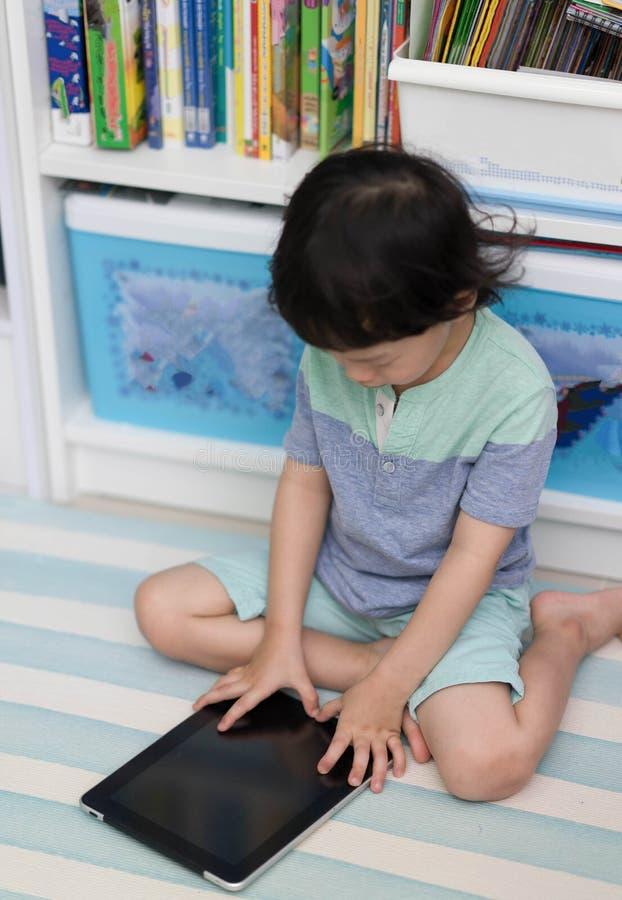Muchacho tailandés del niño que juega o que lee la tableta para el estudio en sitio en BO imagen de archivo
