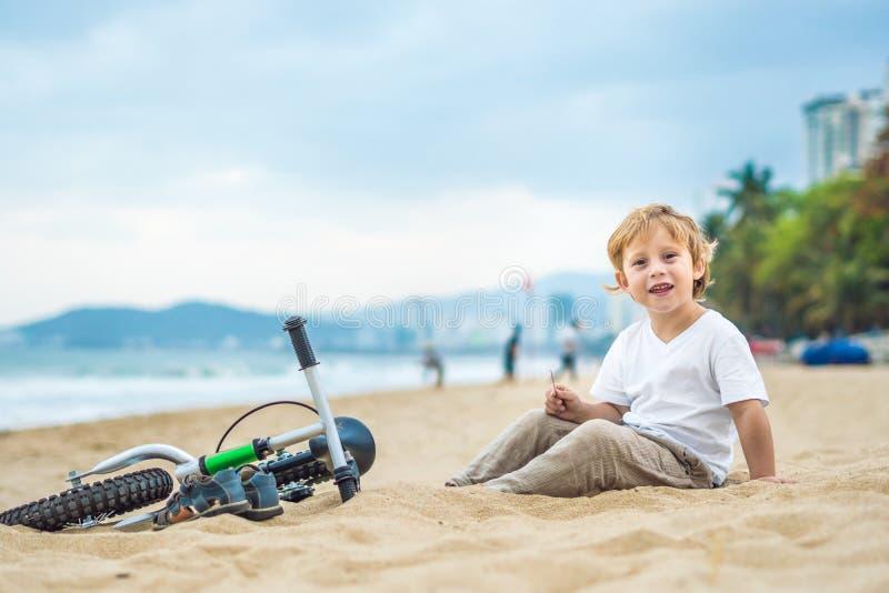 Muchacho y bicicleta rubios activos del niño cerca del mar Niño del niño que sueña y que se divierte en día de verano caliente al fotografía de archivo