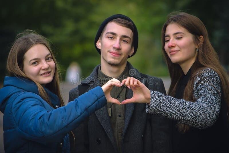muchacho y dos muchachas que forman sus manos a la forma del corazón foto de archivo libre de regalías