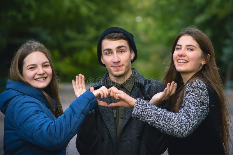 muchacho y dos muchachas que forman sus manos a la forma del corazón fotografía de archivo