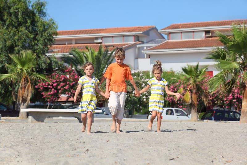 Muchacho y dos muchachas que recorren en la playa foto de archivo
