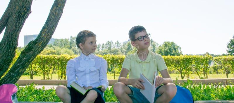 muchacho y estudiantes que sientan los libros de lectura en la calle fotos de archivo
