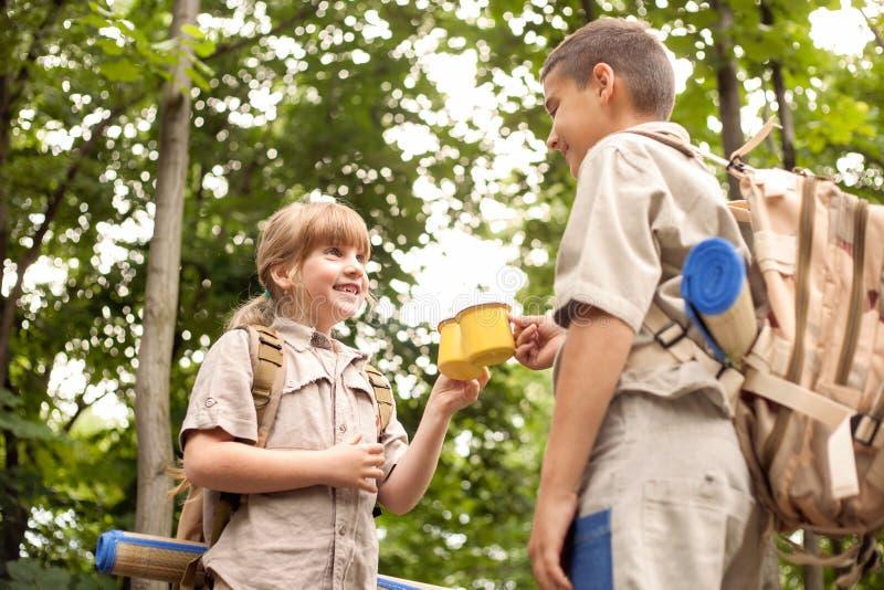 Muchacho y girls scout en una acampada en el bosque fotos de archivo