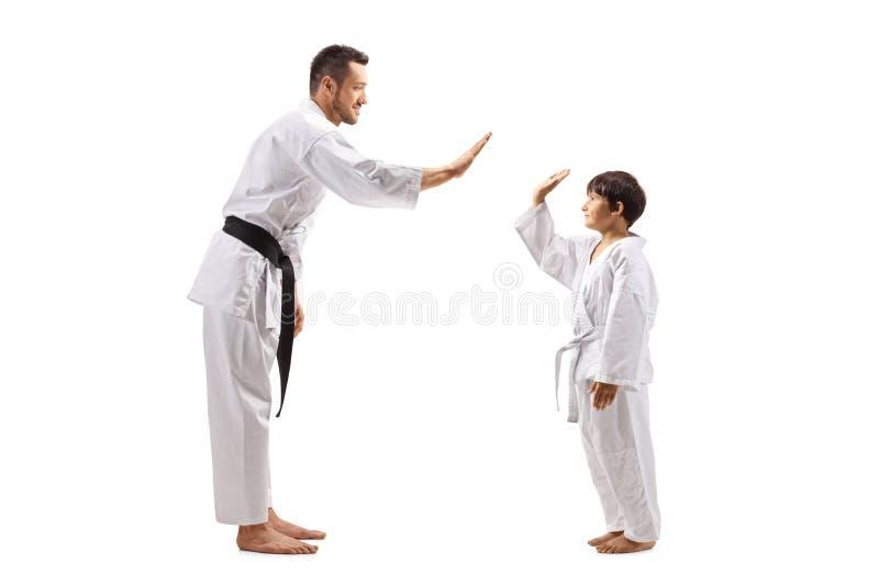 Muchacho y hombre en gesticular de los kimonos del karate alto-cinco foto de archivo libre de regalías