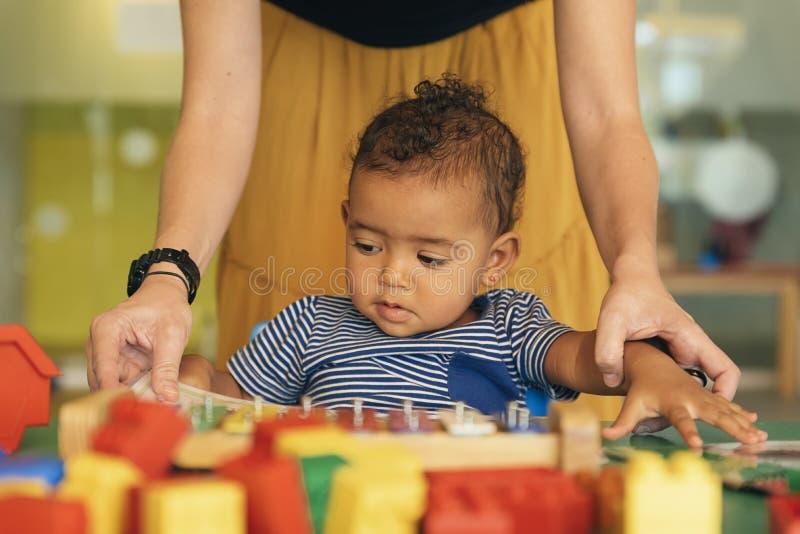 Muchacho y madre del niño que miran un libro educativo imagen de archivo libre de regalías