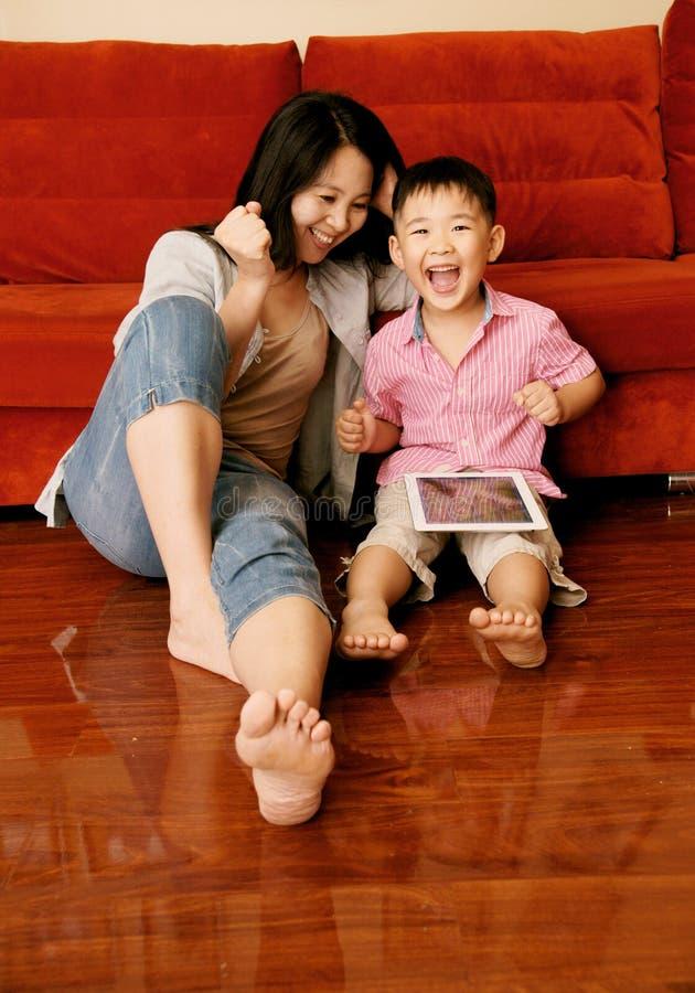 Muchacho y madre que juegan a juegos con la tablilla foto de archivo